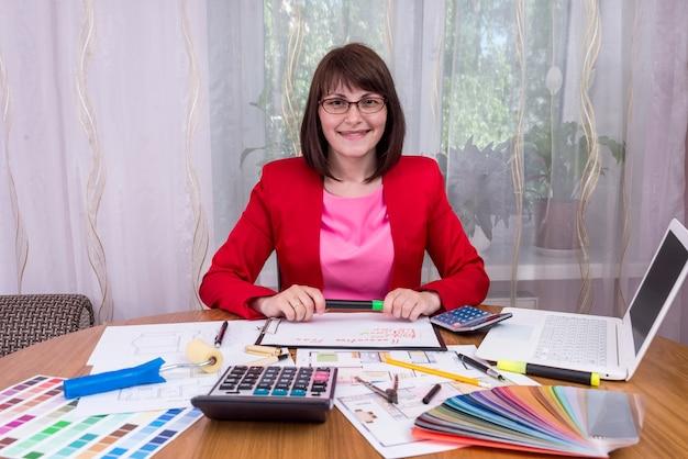 Designer in possesso di pennarello e sorridente sul posto di lavoro