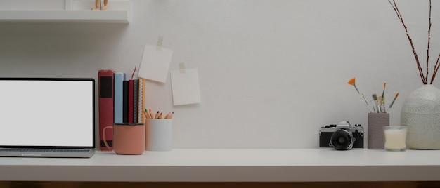 Casa di design con un laptop, libri e decorazioni sul tavolo bianco