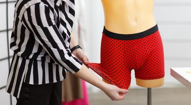 Il designer di intimo maschile controlla la resistenza del tessuto del prodotto finito su un manichino.