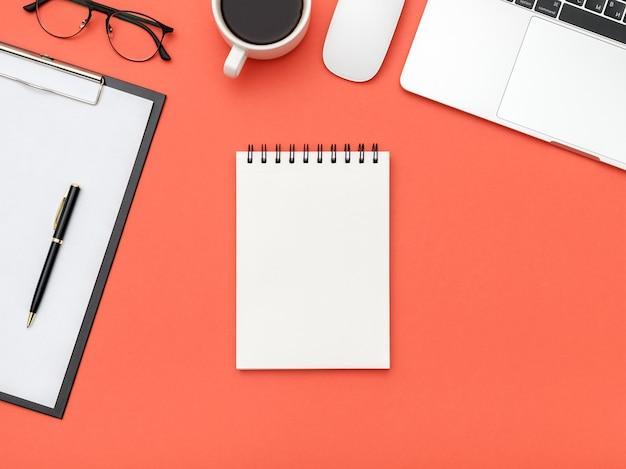 Tavolo scrivania da ufficio di design con pagina vuota del taccuino e computer portatile
