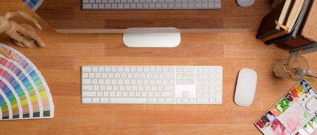 Scrivania del progettista con il computer, lo strumento della pittura, i libri e le decorazioni sulla tavola di legno