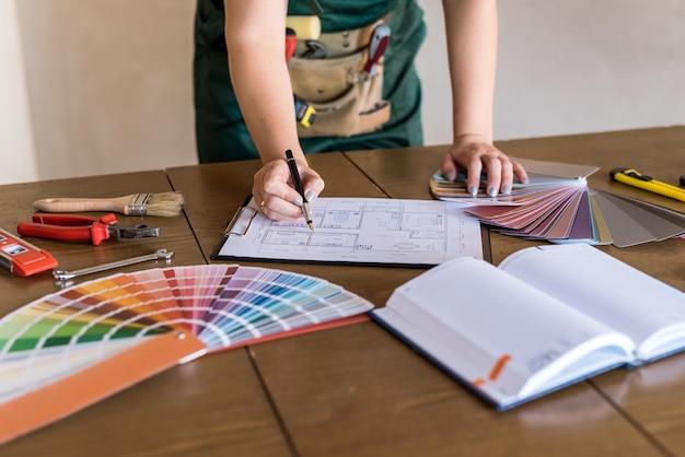 Luogo di lavoro del designer con planimetria della casa, campionatore di colori e strumenti
