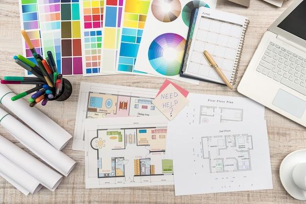 Vista dall'alto sul posto di lavoro del progettista. piano della casa con tavolozze colorate, laptop e tazza di caffè