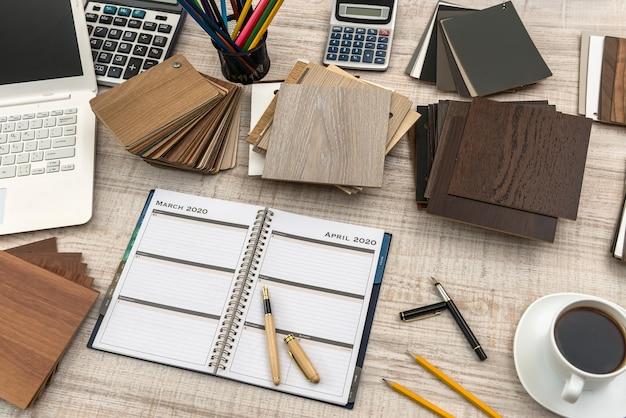 Area di lavoro del designer con alcuni campioni di colore in legno, blocco note vuoto, laptop e penna