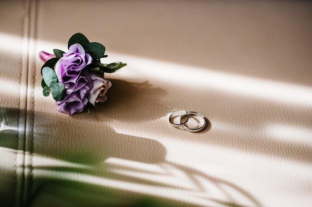 Designer silver due fedi nuziali e fiori su fondo beige con copia spazio. fidanzamento. matrimonio di lusso e concetto di matrimonio.