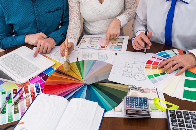 Team di designer che discute di campionatore di colori, pittura e ristrutturazione