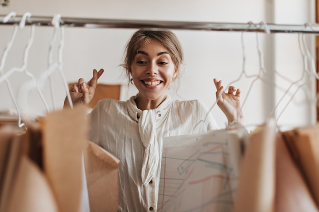 Designer in camicetta bianca incrocia le dita