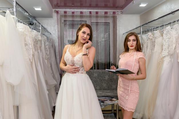 Designer con blocco note e cliente donna nel negozio di matrimoni