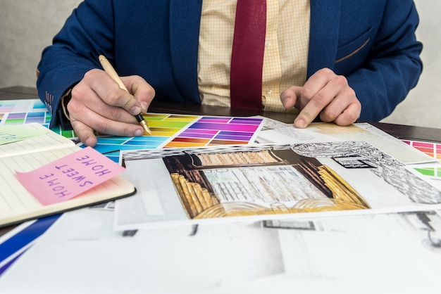 Designer lavora in ufficio con abbozzo creativo domestico e campione di colore per la ristrutturazione moderna. progetto di architetto