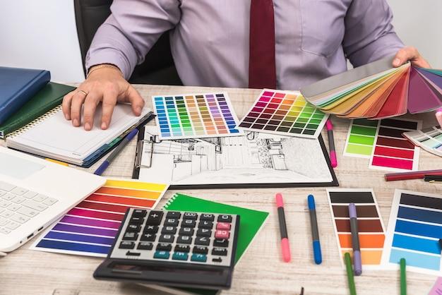 Designer che lavora in ufficio all'idea di un moderno progetto di casa. schizzo dell'appartamento e selezione del colore