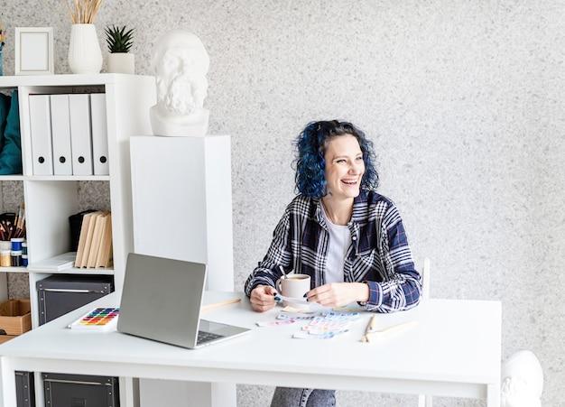Designer che lavora con tavolozze di colori e laptop nel suo studio d'arte