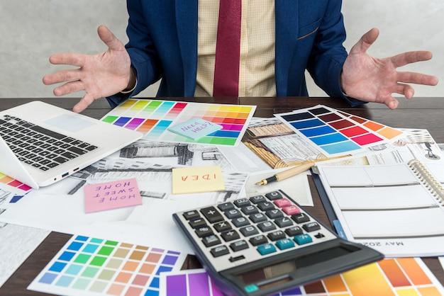 Designer che lavora con disegni domestici e campionatori di colori per interni moderni. progetto archtercture, posto di lavoro in ufficio