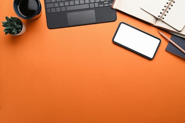 Posto di lavoro di design con smart phone, tastiera, notebook e copia spazio su sfondo arancione.