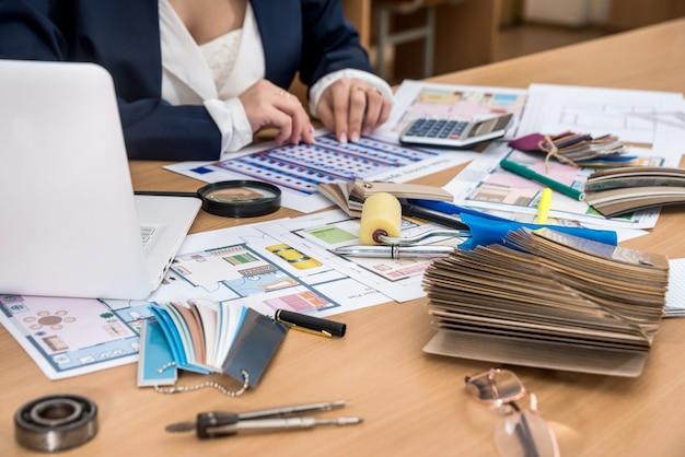 Il designer lavora in ufficio con campioni di colori, un laptop e una pianta dell'edificio