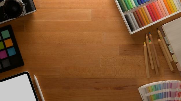 Area di lavoro di design con controllo del colore, strumenti di pittura, mock up tablet e forniture