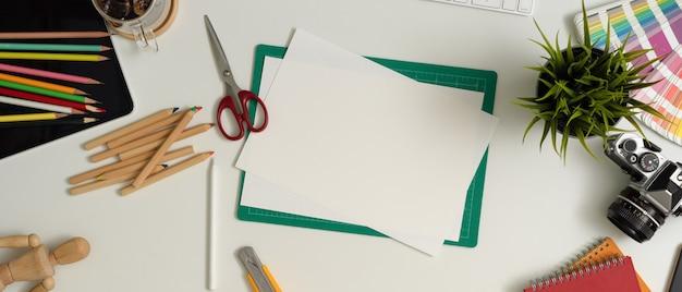 Area di lavoro del progettista con carta per schizzi, strumenti di pittura, macchina fotografica, forniture e decorazioni sul tavolo bianco