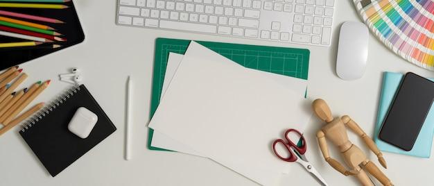 Area di lavoro di design con carta per schizzi, strumenti di pittura, forbice, computer, smartphone e forniture sul tavolo bianco