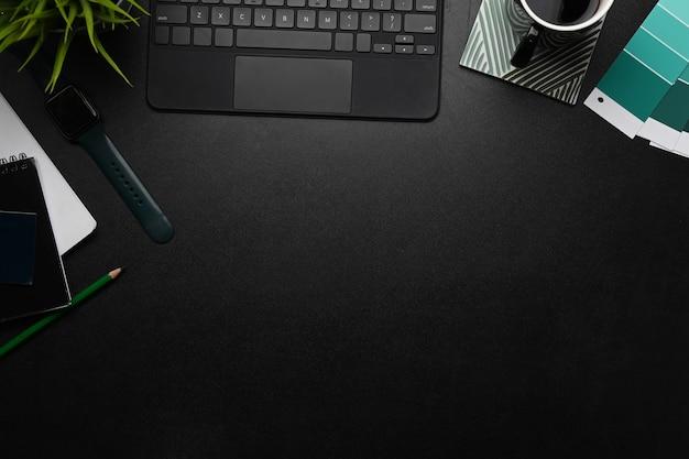 Area di lavoro di design con smart watch, notebook, tastiera e campioni di colore sul tavolo nero.