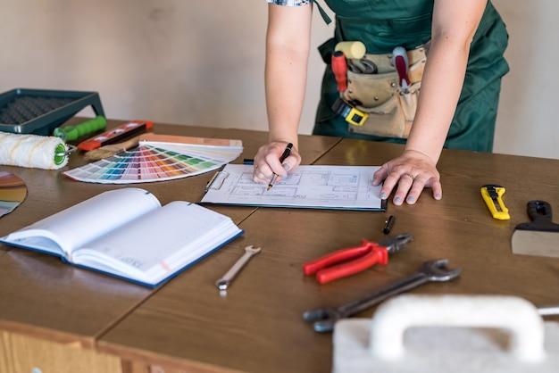 Luogo di lavoro dei progettisti con pianta della casa, campionatore di colori e strumenti