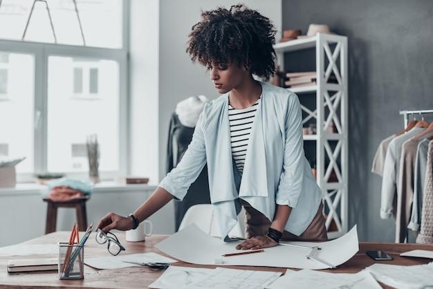 Disegnare nuovi vestiti. bella giovane donna africana che mette gli occhiali sulla scrivania