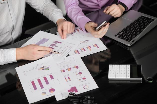 Scrivania in ufficio con grafici, un computer portatile e le mani degli uomini