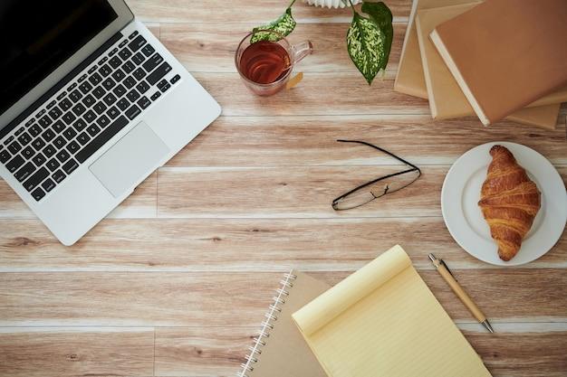 Scrivania dello studente con laptop aperto, libri, pianificatore, tazza di tè e croissant