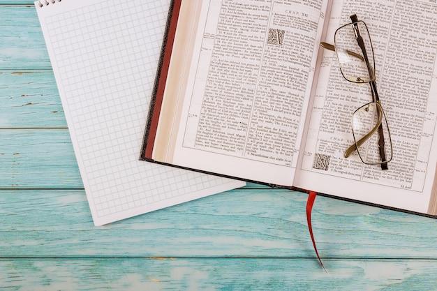 Il tavolo da scrivania ha aperto la sacra bibbia da vicino il tempo di preghiera sul blocco note