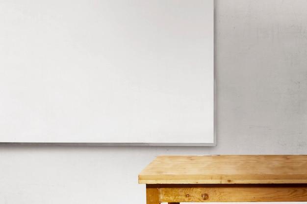 Scrivania e lavagna all'interno dell'aula con sfondo muro bianco