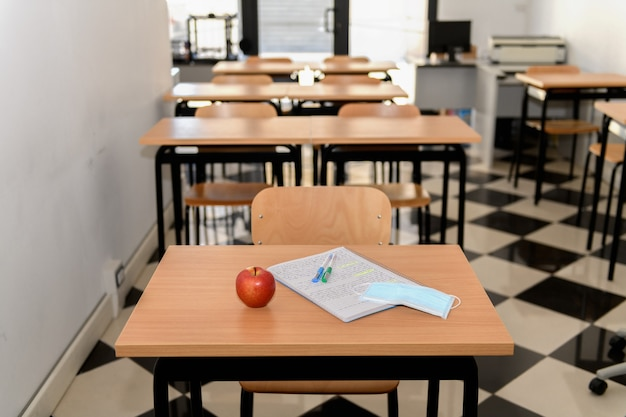 Scrivania con una mela, una mascherina medica e un quaderno in un'aula vuota
