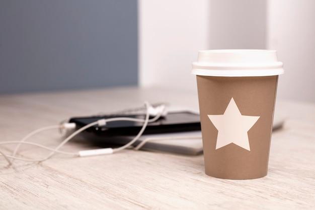 Scrivania con bicchiere di caffè caldo telefono con auricolari