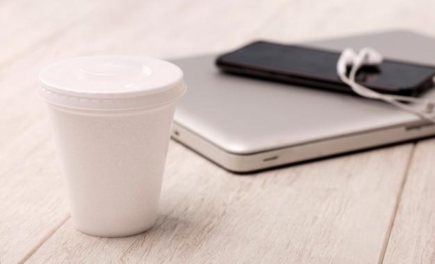 Scrivania con bicchiere termico di caffè sul tavolo con computer phone e auricolari