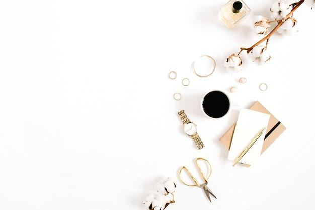 Scrivania con collezione di accessori donna orologi dorati, forbici, tazza da caffè, quaderno e ramo di cotone su sfondo bianco. lay piatto