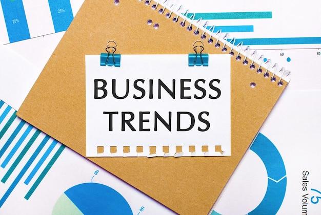 Sul desktop ci sono grafici e diagrammi blu e azzurro, un taccuino e un foglio di carta con clip blu e testo business trends. vista dall'alto. concetto di affari