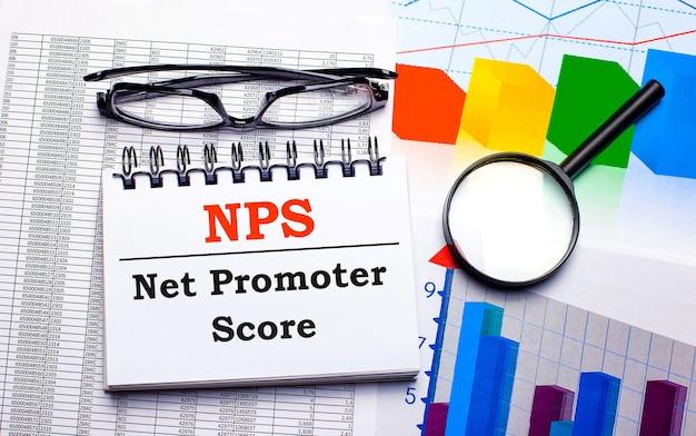 Sul desktop ci sono occhiali, una lente d'ingrandimento, grafici a colori e un taccuino bianco con il testo nps net promoter score. concetto di affari. vista dall'alto