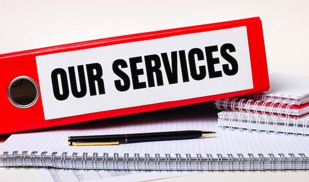 Sulla scrivania ci sono quaderni, una penna e una cartellina rossa per i documenti con il testo i nostri servizi. concetto di affari