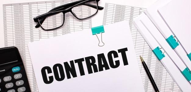 Sul desktop ci sono rapporti, documenti, occhiali, una calcolatrice, carta e penna con il testo contratto. concetto di affari