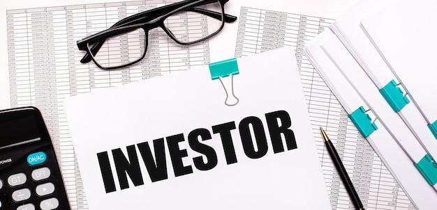 Sul desktop ci sono report, documenti, occhiali, una calcolatrice, carta e penna con il testo investor. concetto di affari
