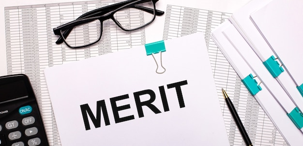 Sul desktop ci sono relazioni, documenti, occhiali, una calcolatrice, carta e penna con il testo merit. concetto di affari