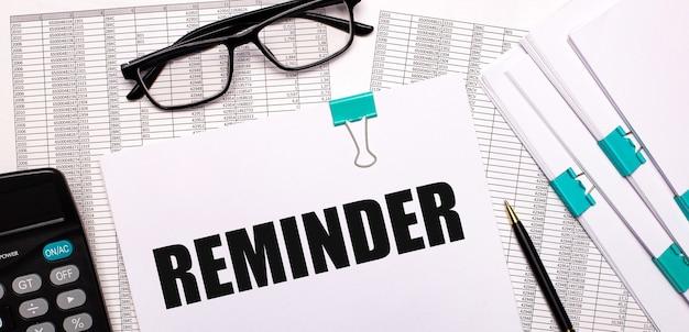 Sul desktop ci sono report, documenti, occhiali, una calcolatrice, carta e penna con il testo promemoria. concetto di affari