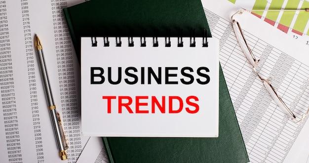Sul desktop ci sono report, occhiali, una penna, un diario verde e un taccuino bianco con le parole tendenze aziendali. primo piano sul posto di lavoro. concetto di affari