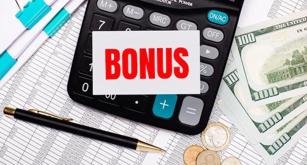 Sul desktop ci sono rapporti, una penna, contanti, una calcolatrice e una carta con il testo bonus. concetto di affari