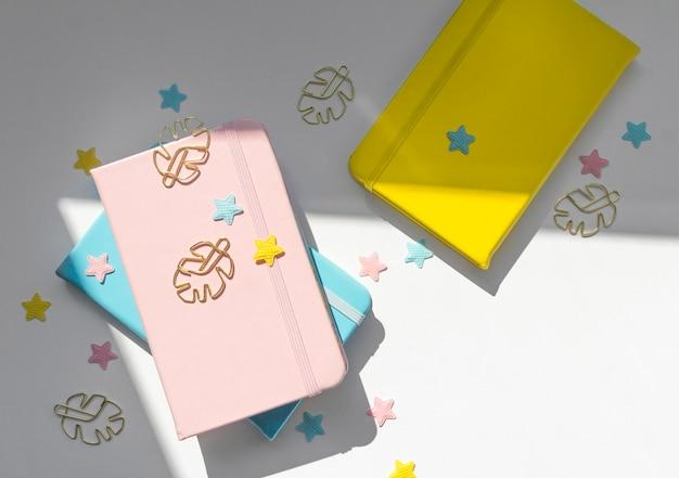 Composizione piatta da tavolo femminile con blocchi per appunti rosa, gialli e blu, stelle e clip dorate monstera