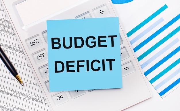 Sul desktop c'è una calcolatrice bianca con un adesivo blu con il testo budget deficit, una penna e dei report blu. concetto di affari
