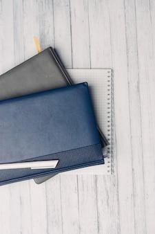 Blocco note desktop e documenti ufficio sfondo di legno vista dall'alto