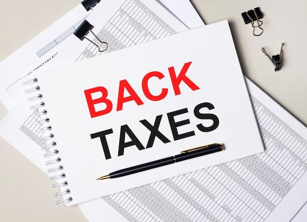 Sulla scrivania ci sono documenti, penna, graffette nere e un quaderno con la scritta back taxes. concetto di affari