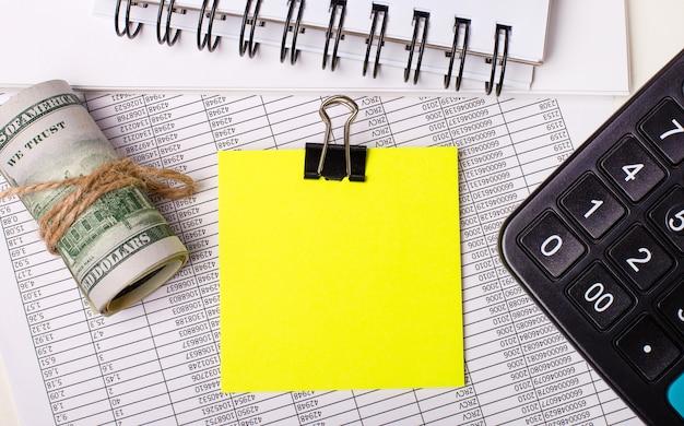 Sul desktop ci sono report, taccuini, una calcolatrice, contanti e un adesivo giallo con un posto dove inserire il testo. modello. concetto di affari