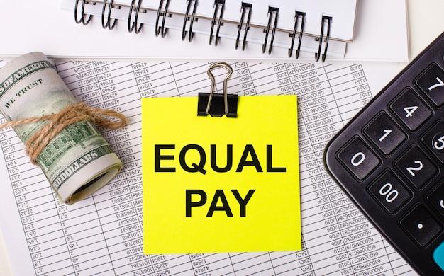 Sul desktop ci sono rapporti, taccuini, una calcolatrice, una cassa e un adesivo giallo con la scritta equal pay. concetto di affari