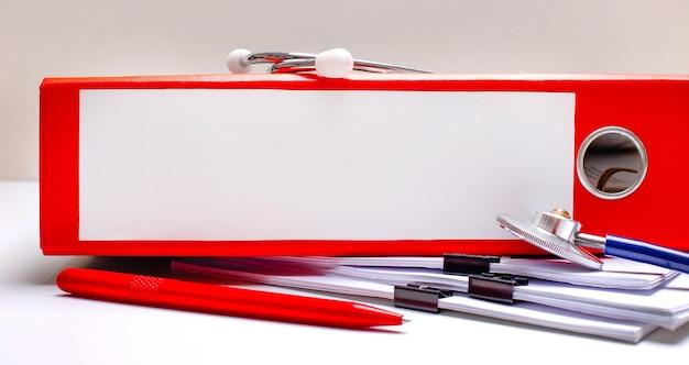 Sul desktop c'è uno stetoscopio, una penna, una cartella rossa con file con un posto dove inserire il testo. concetto medico