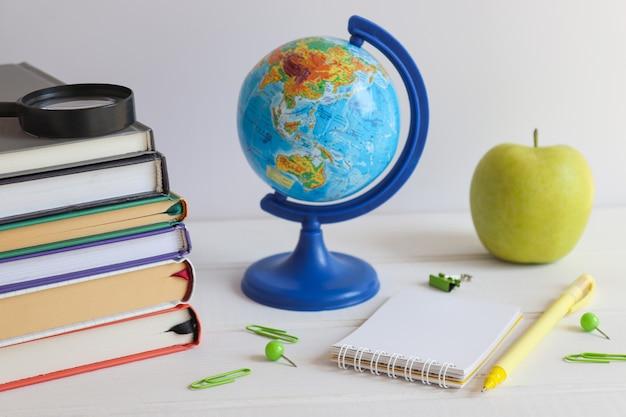 Desktop con libri taccuino globo penna mela verde e lente d'ingrandimento