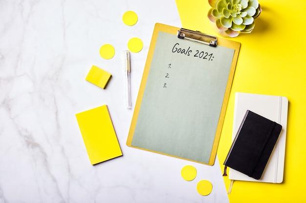 Desktop con appunti con mockup elenco obiettivi e forniture per ufficio. home office, pianificazione del concetto di definizione degli obiettivi. flatlay, vista dall'alto